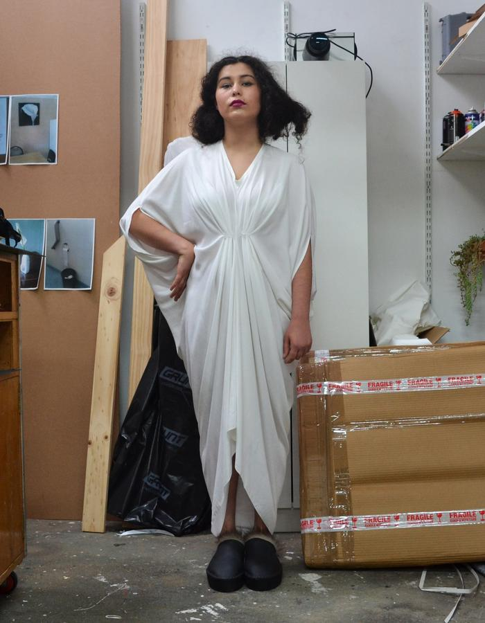 White rayon dress cut from a single piece of fabric with box-pleats in the back and gathered front.