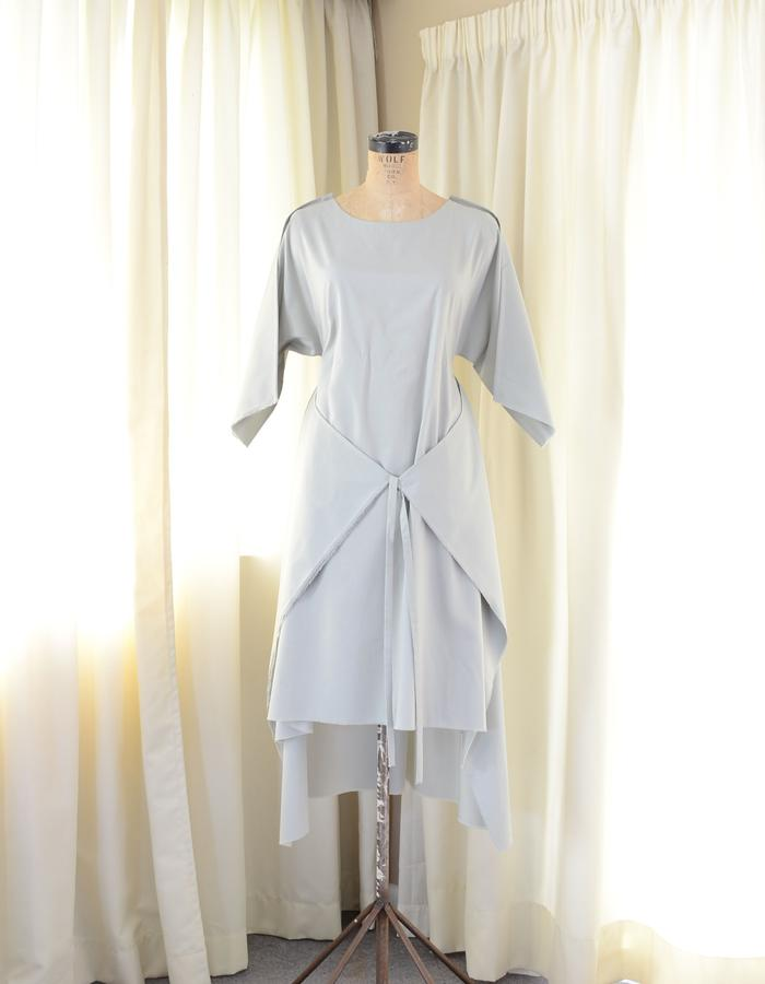 A 2-D dress with external french seams with waist ties and selvedge cuffs.