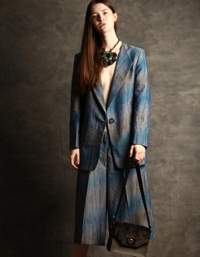 Wrinkled fused blue/grey cotton suit with bermuda style pants.