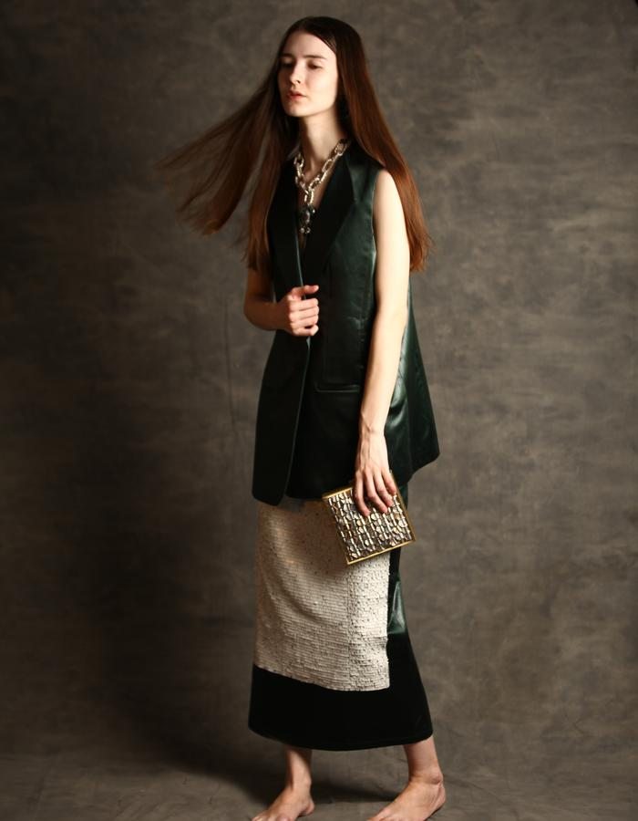 Sleeveless jacket and a long skirt with sequined embroidery in leather finish coated green fabric.