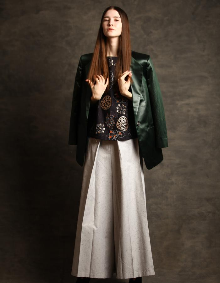 Constellation embroidered top,pleated cotton pants and Leather finish coated green fabric suit blazer.