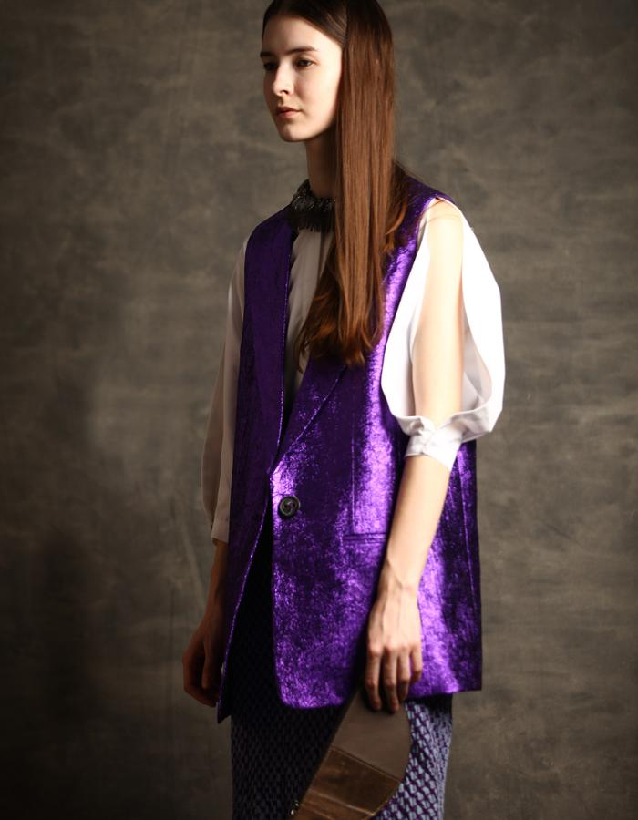 Oversized sleeveless jacket in wrinkled poly blend and a white cut out sleeve shirt.