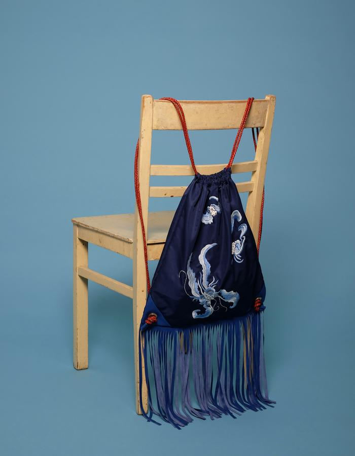 alan auctor ss16 embroidered string backpack hanging on a chair