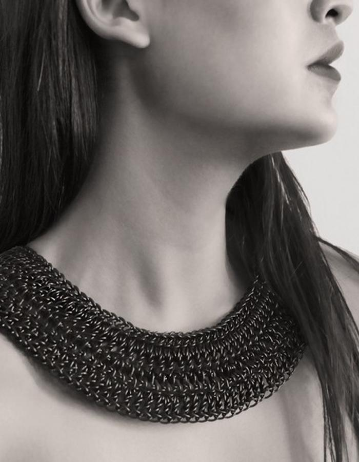 0.2 Necklace: is hand knitted with crochet technique and combines different stitches along the planar and concentric surface. It has steel terminations engraved by sublimation process.