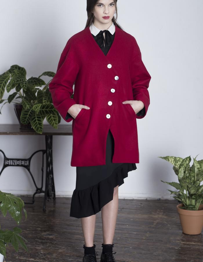 Zoe Carol Womenswear black wool asymmetric ruffle hem skirt and fitted black and white silk and wool collared top and red wool drape back coat
