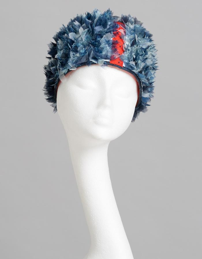 Head hugging domed hat, covered with blue handmade cyanotype silk flowers with a contrasting orange band