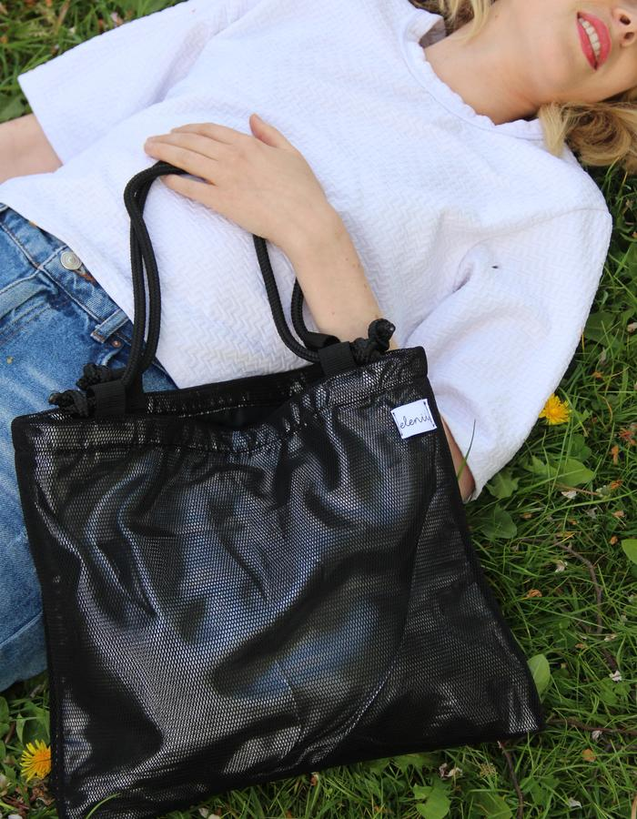 BLACK NEOPRENE TOTE BAG WITH METALLIC SILVER LAYER AND BLACK ROPE STRAPS.