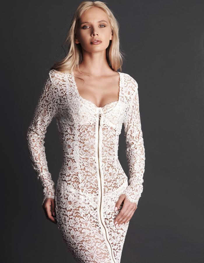 A timelessly feminine and dramatic floor-length gown from intricately corded French lace: this dress is the epitome of luxury and decadence. Full length sleeves end with delicate lace eyelash scallops that wrap around the wrist. A gold toned double ended zip features down the centre front to enable the wearer to reveal and conceal as they wish, whether it be either plunging the neckline or lengthening the seductive front split. Designed to flatter and enhance the female from this elegant creation is an esse