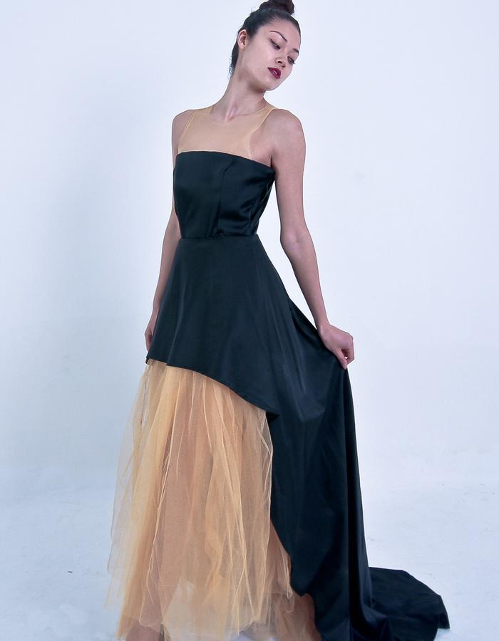 The gown is a mixture of metallic gold tules and black satin fabrics.