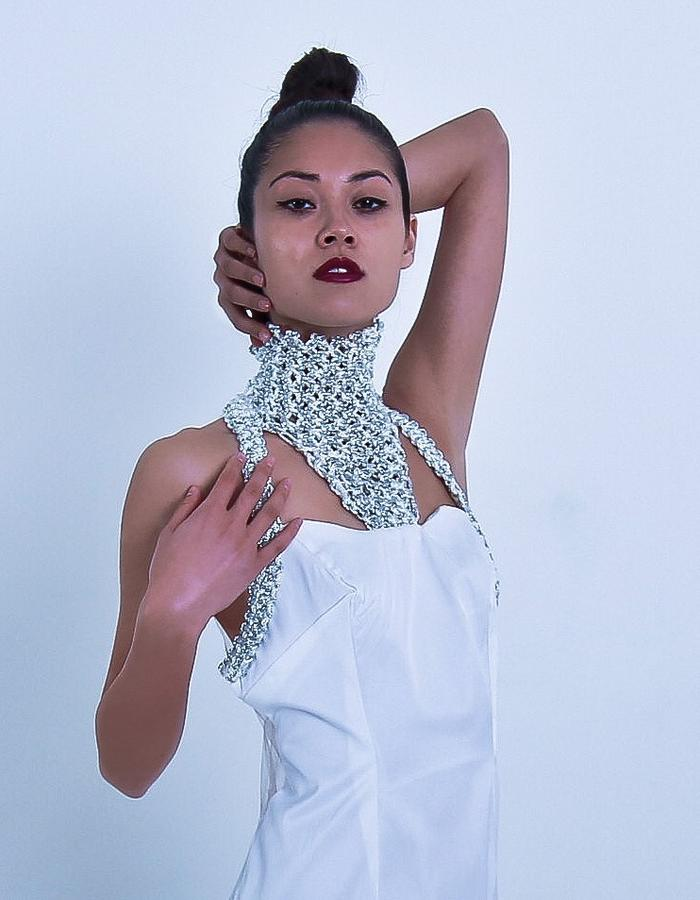 A sleeveless long evening gown in white colour and a hand crafted embellished betails around the collar part. An opener and mid-back invisible zip