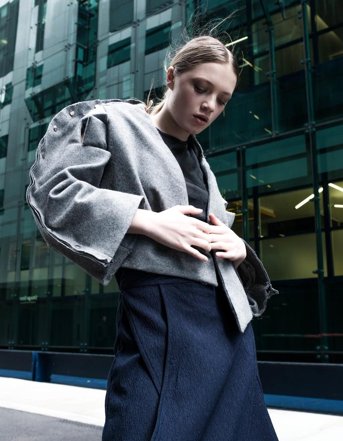 Idō - Look 1. Cropped grey woollen jacket with rivets and sleeve detail + Layered wrap-around cullotes